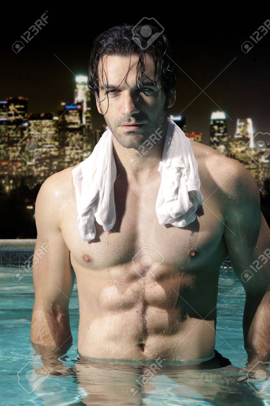 Sexy male model with great abs and muscular body in swimming pool at night with city skyline background Stock Photo - 14523761