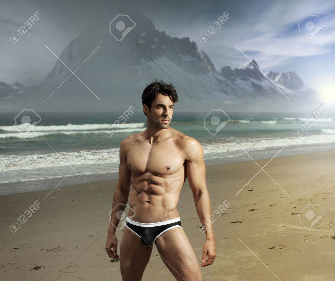 Muscular fit sexy guy on remote scenic beach location with dramatic mountains in background Stock Photo - 14732863
