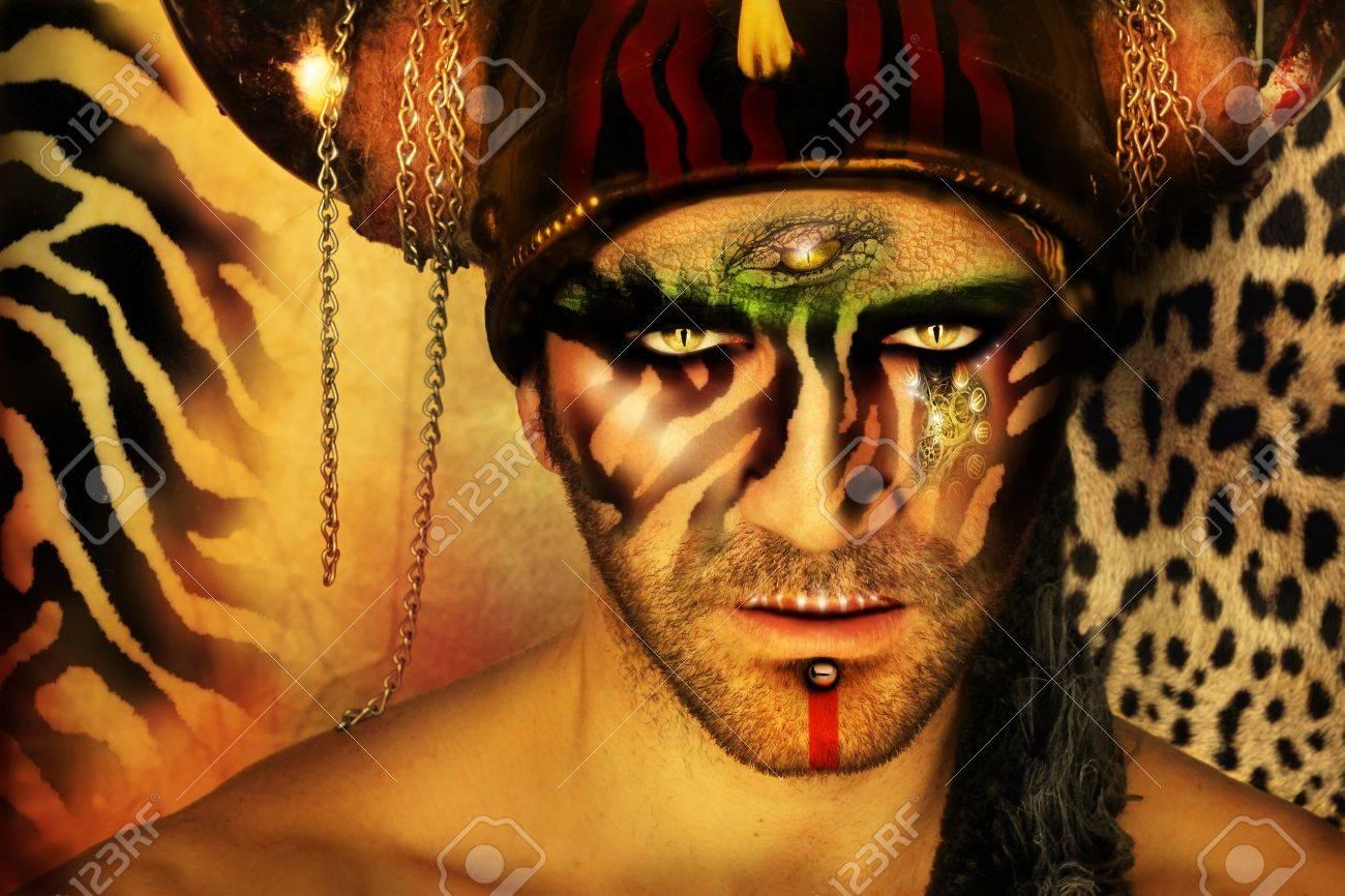 Banque d\u0027images , Portrait concept de mode stylisée d\u0027un jeune homme avec maquillage  tribal et éléments d\u0027origine animale devant un fond imprimé animal