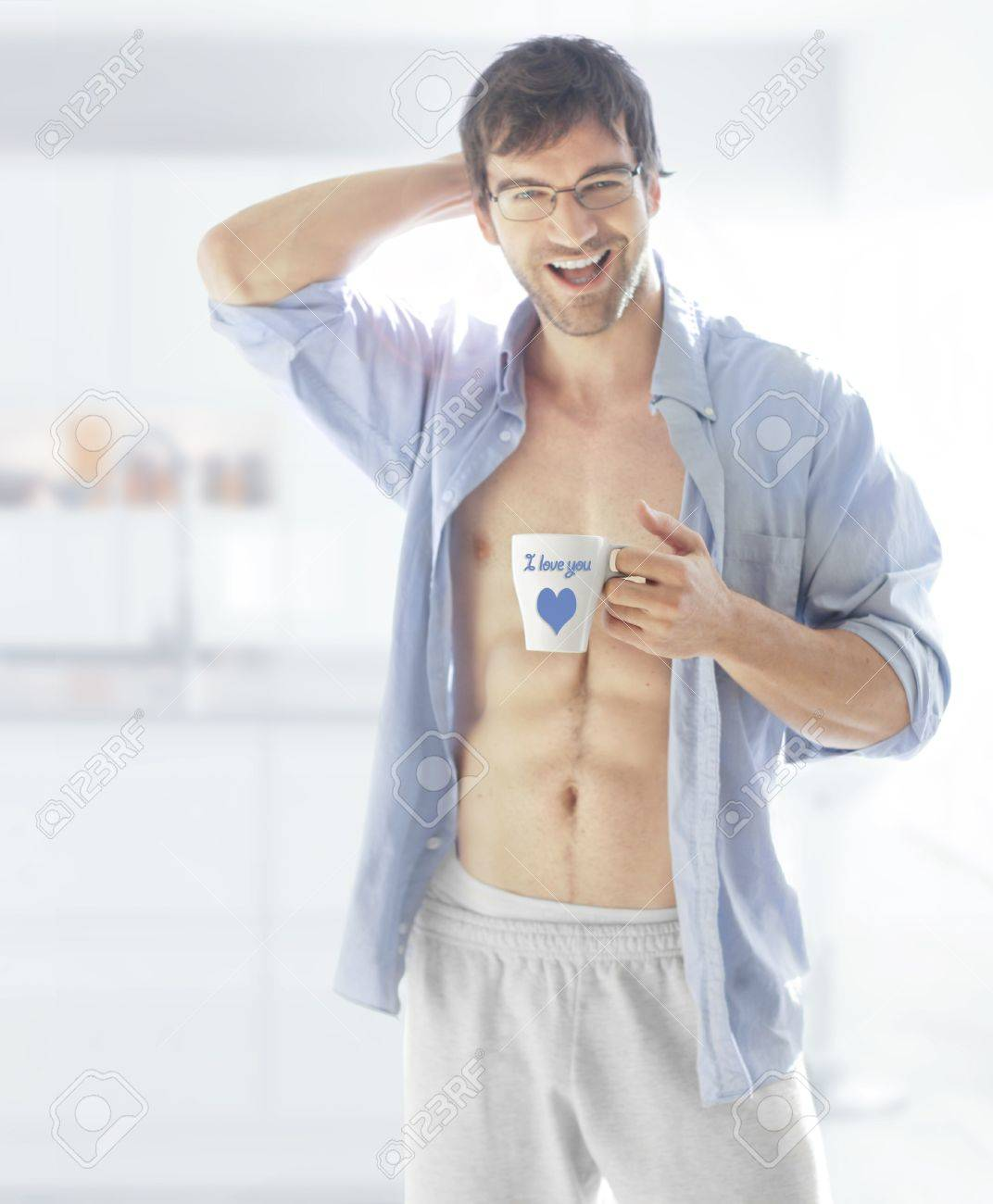 A hot looking smiling male model holding coffee cup that reads &quot,I Love You&quot, with a heart symbol Stock Photo - 17383396