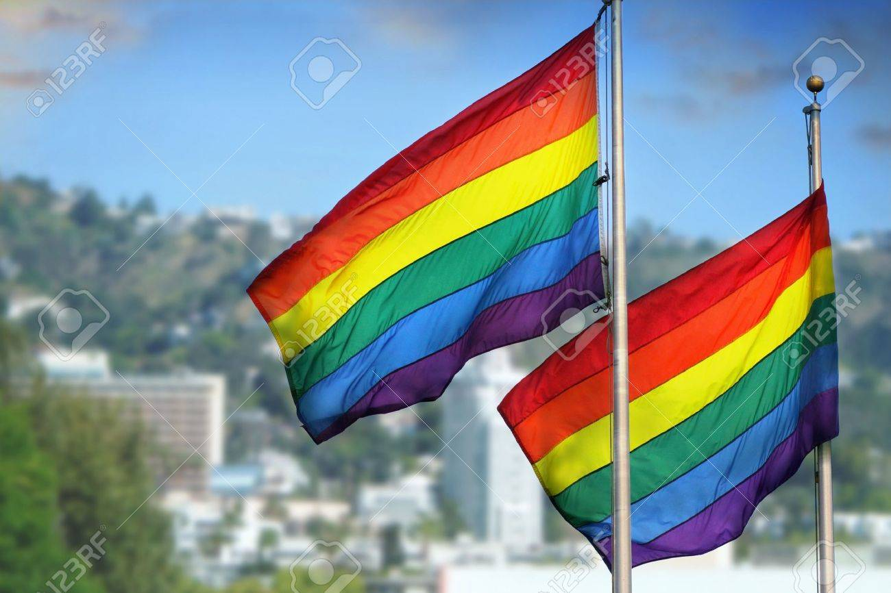 Pics photos desk with flag in background photographic print by - Gay Flag A Pair Of Rainbow Flags Waving In Wind Against City Background Of West