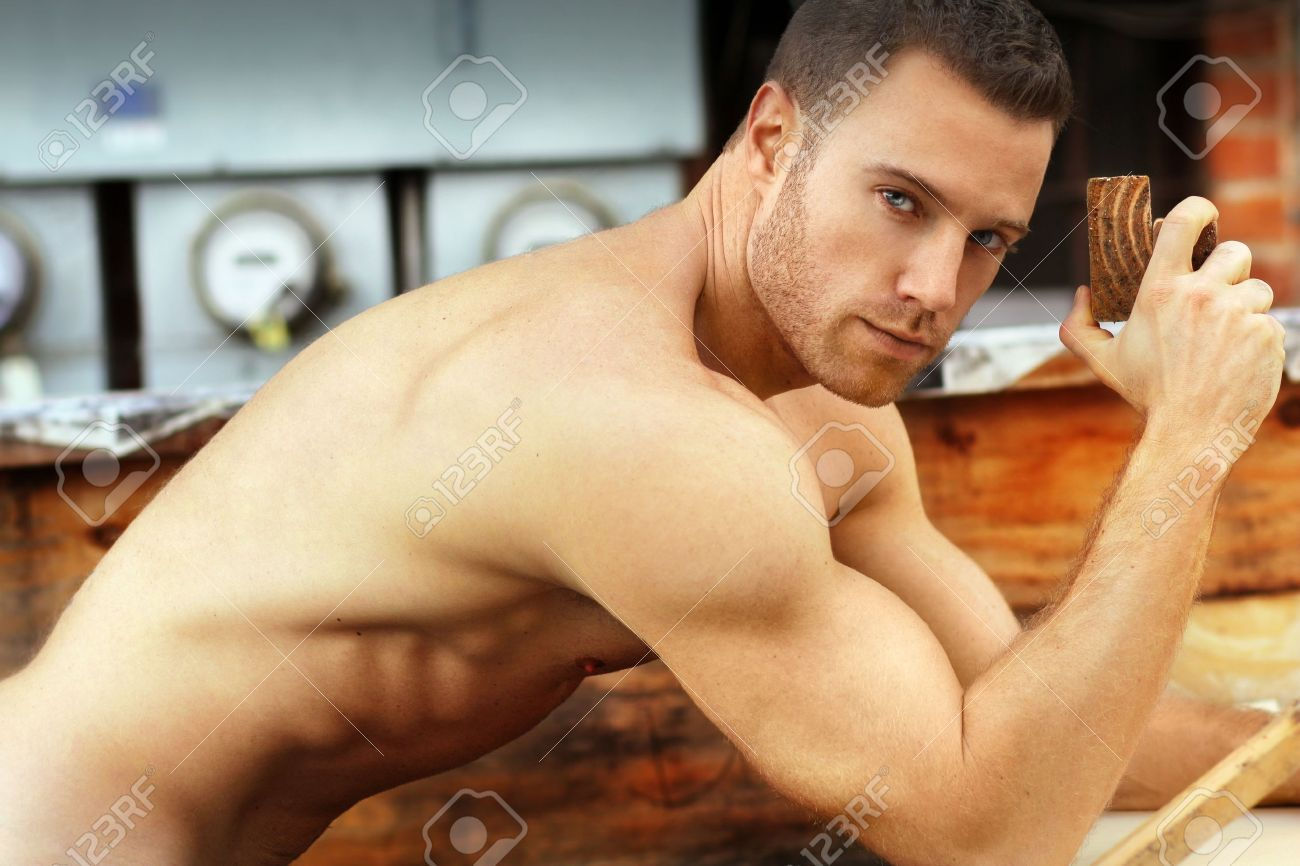 Sexy macho guy shirtless holding working with wood Banque d'images - 25028635