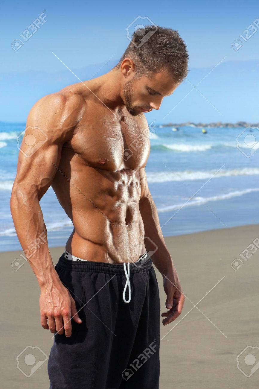Jeune bodybuilder fitness modèle masculin musculaire et en forme sur la plage Banque d'images - 26214697