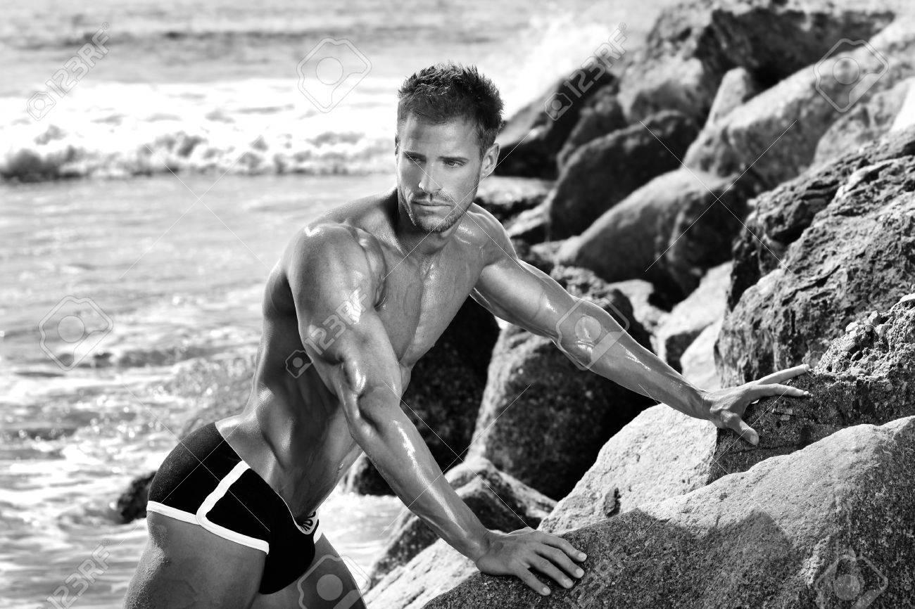 Bodybuilder musculaire sexy posant près de rochers et des océans Banque d'images - 26790124