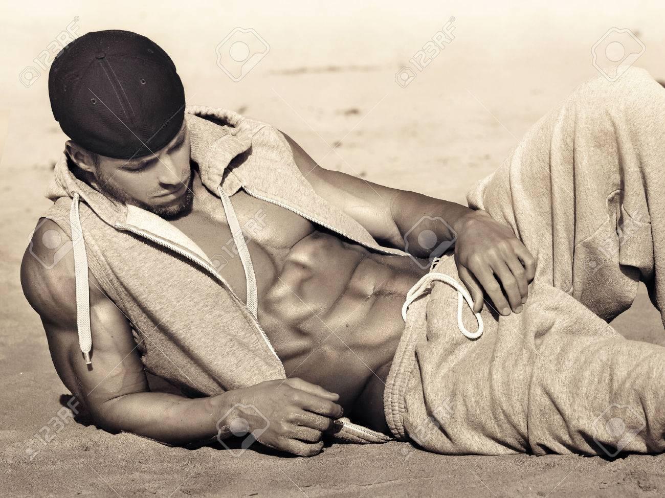 Monter santé jeune modèle masculin avec de grands coups de pied abs retour sur la plage, dans des tons de sépia chaudes Banque d'images - 26925593