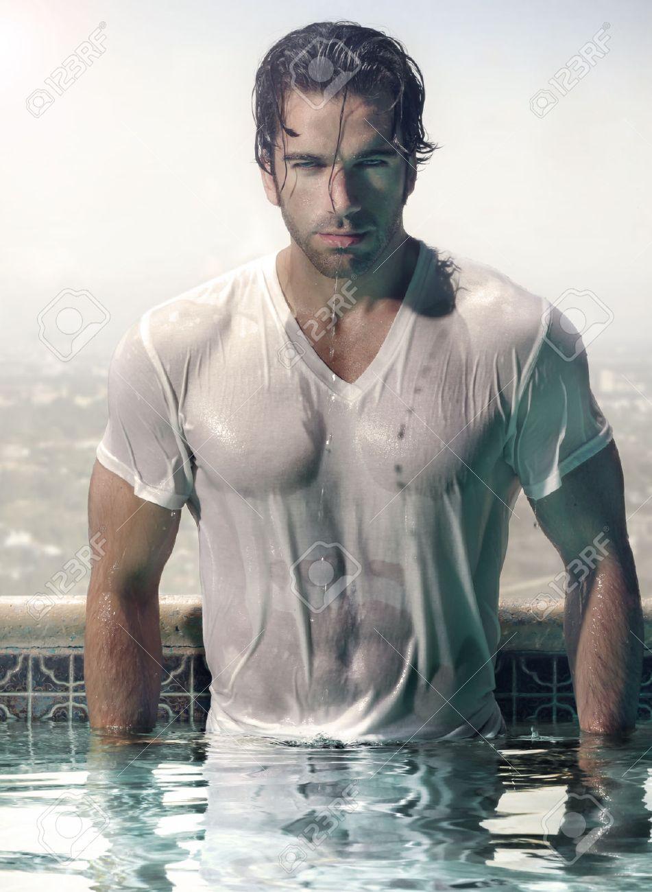Modèle superbe mâle en t-shirt mouillé imbibé debout dans luxueuse piscine avec fond de ville Banque d'images - 27884791