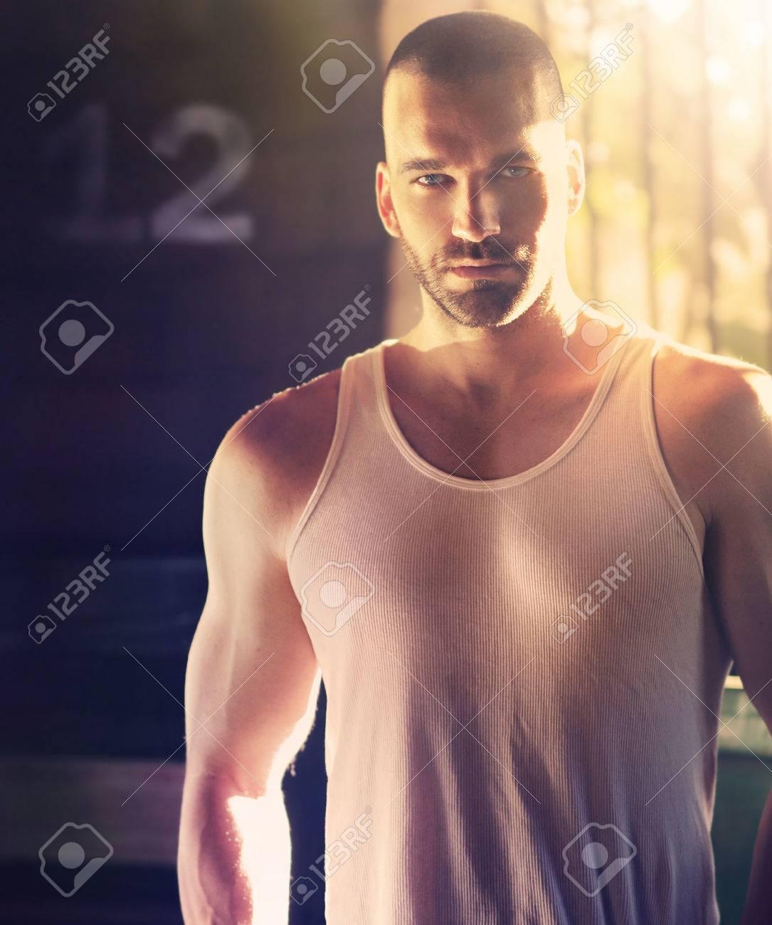 Portrait sexy de l'homme masculin avec la tête rasée en lumière dramatique dur et ombre Banque d'images - 28530638