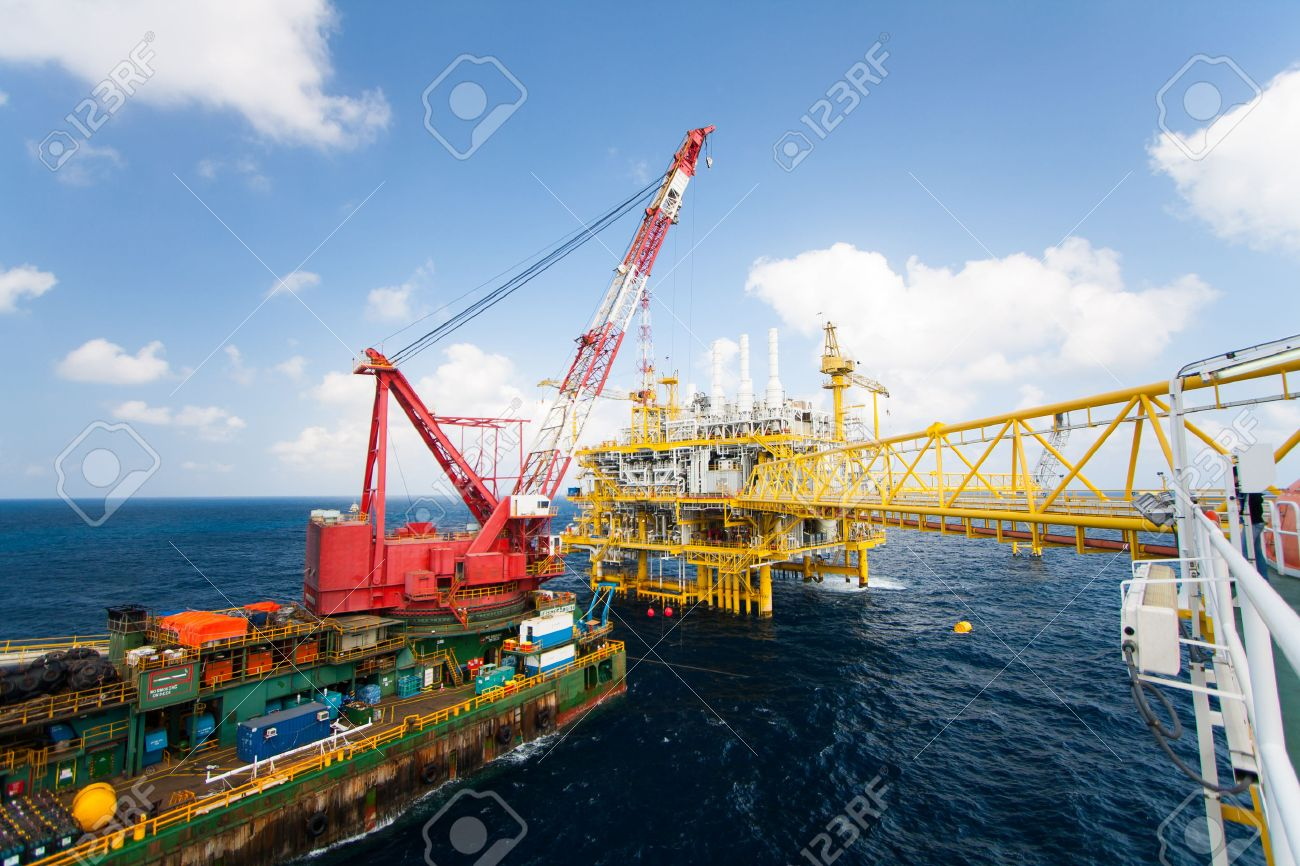 Large crane vessel installing the platform in offshore,crane barge doing marine heavy lift installation works in the gulf or the sea Stock Photo - 25969080