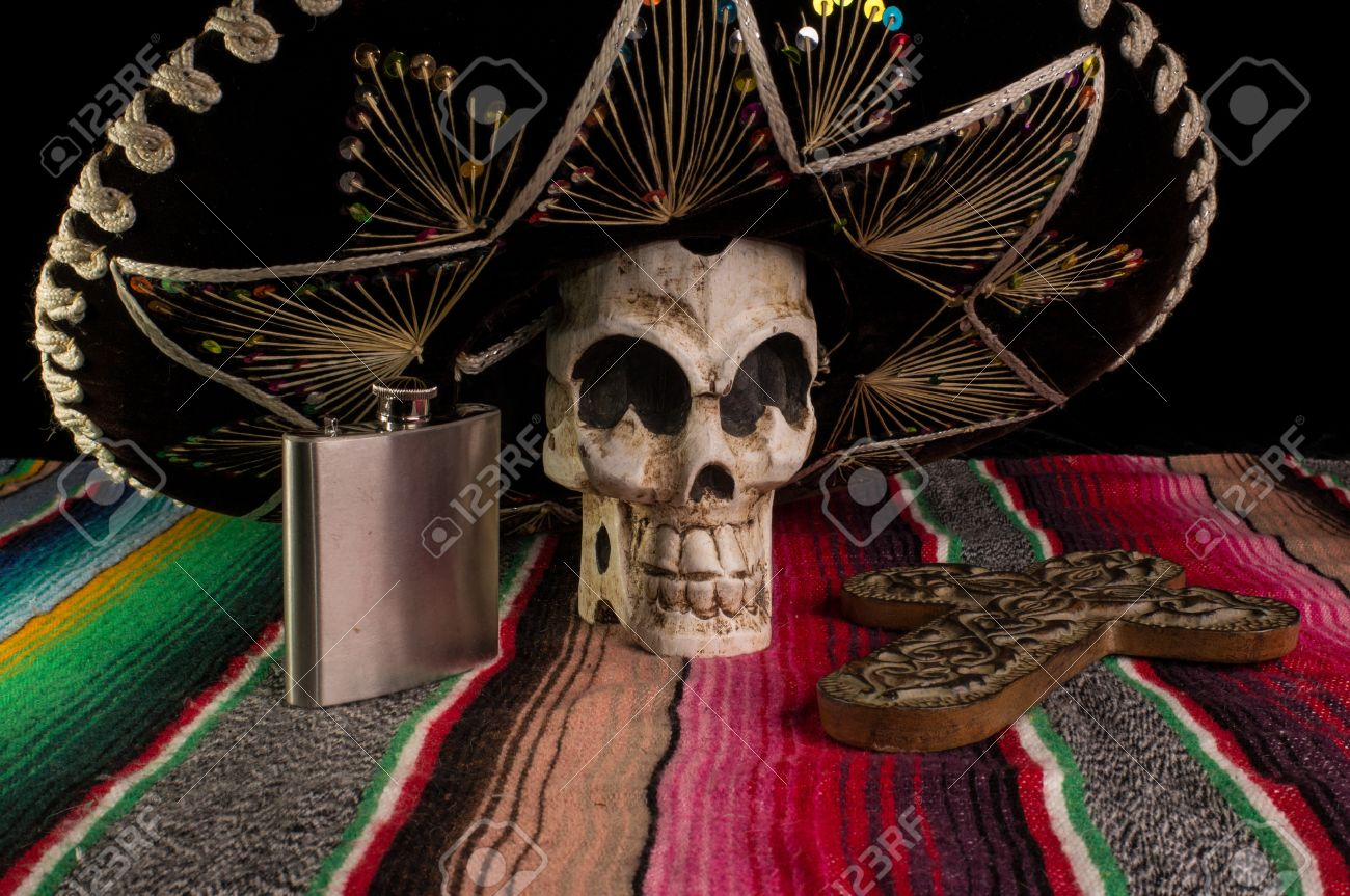 Day of The Dead  Dia de los Muertos  skull with with decorative cross, tequila flask on a traditional mexican blanket Stock Photo - 14989322