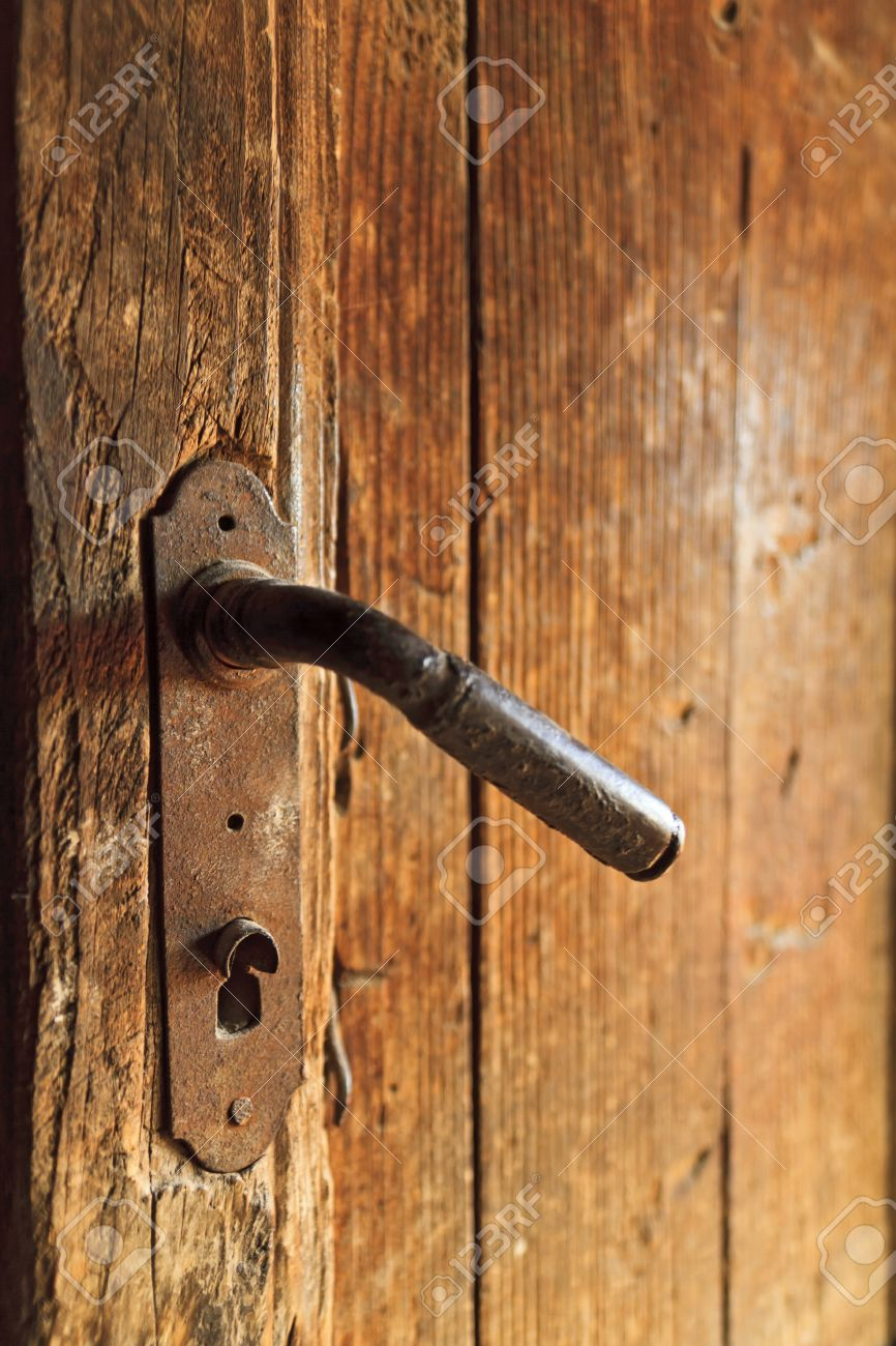 a century old rusty door knob on old wooden door stock photo
