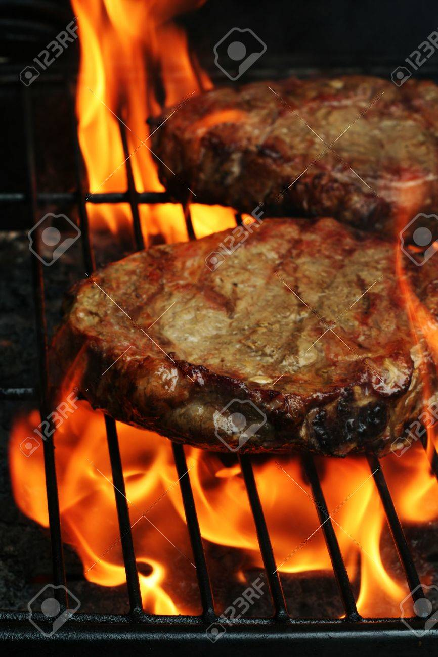 Two Juicy stakes grilling on the barbeque with lots of flame licking around them Stock Photo - 3728857