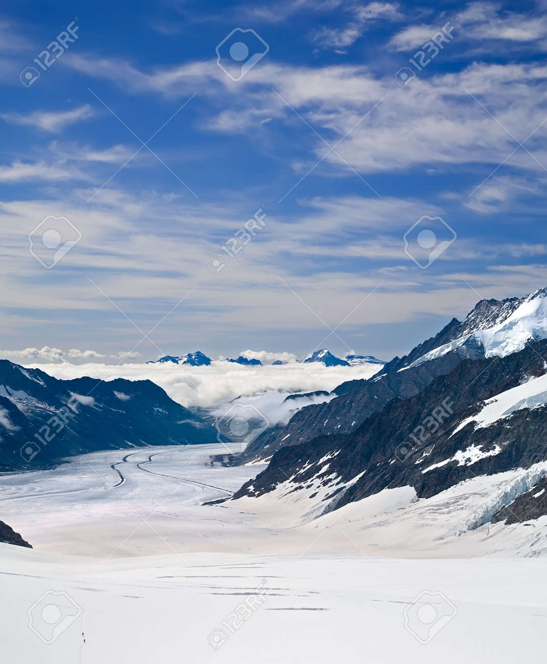 Two Hikers Walking Towards the Aletsch Glacier in the Alps, Switzerland Stock Photo - 3337494