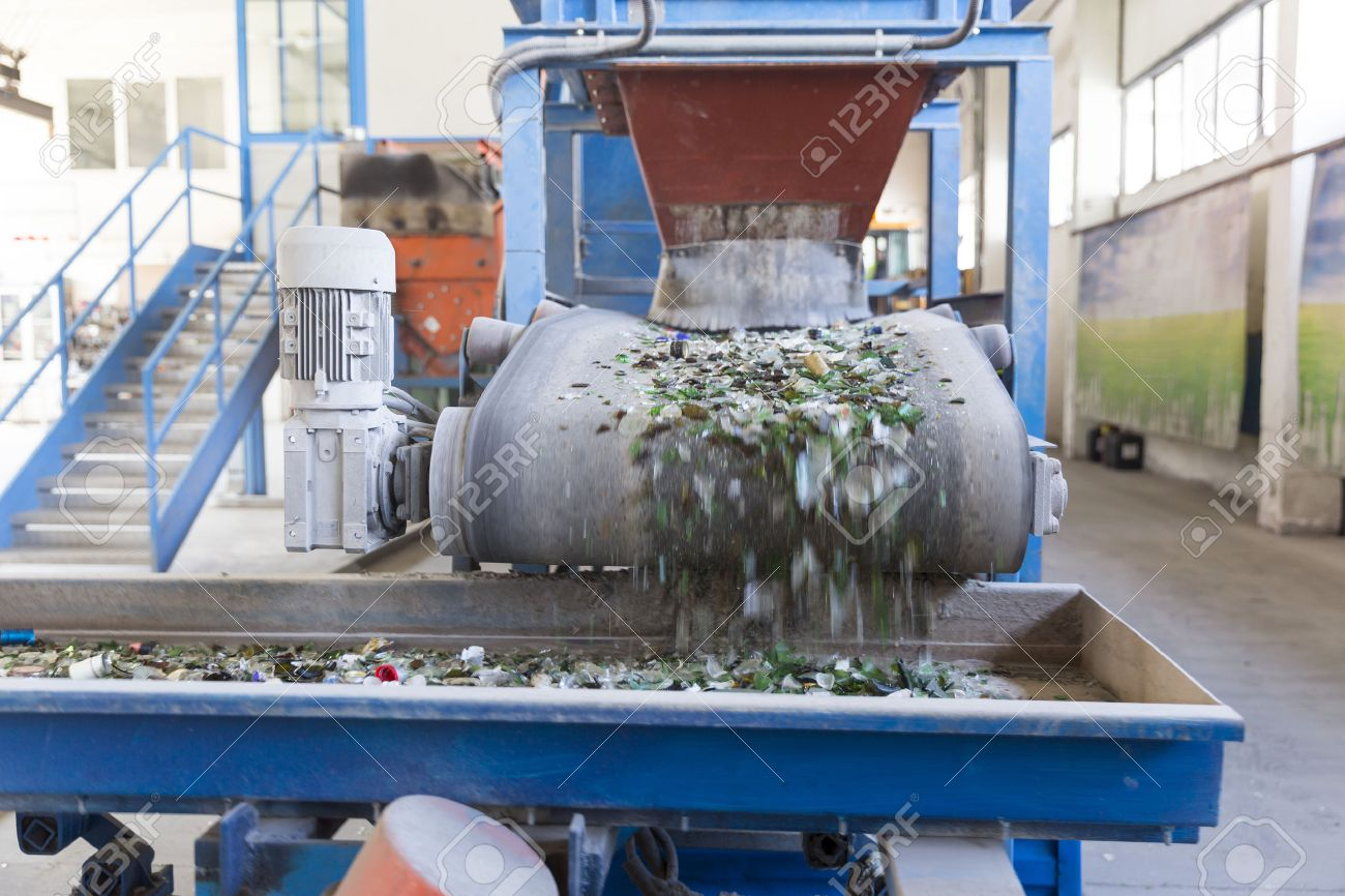 Glass particles for recycling in a machine in a recycling facility. Different glass packaging bottle waste. Glass waste management. Glass recycling is the process of waste glass into usable products. - 62718797