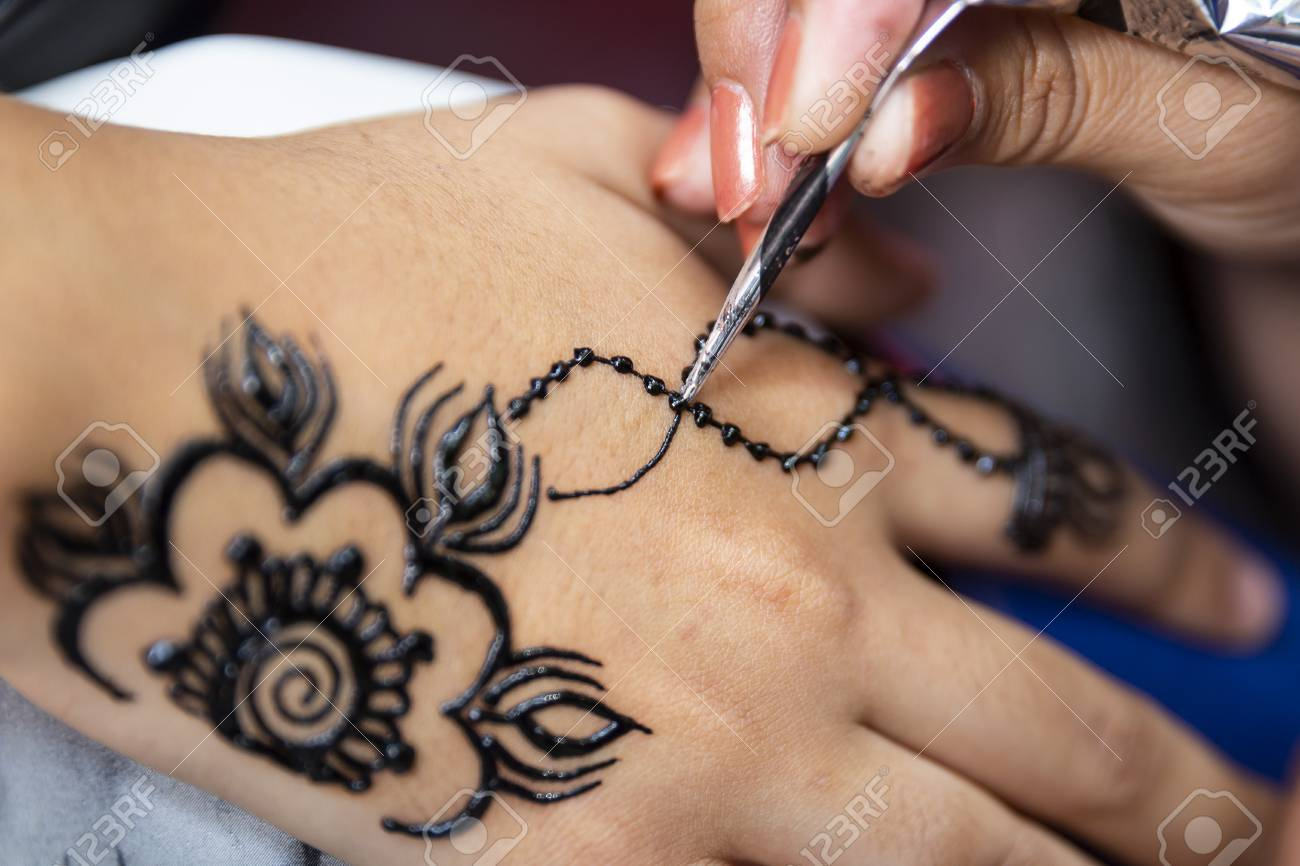 Woman painting black henna tattoo on a girl\'s hand.