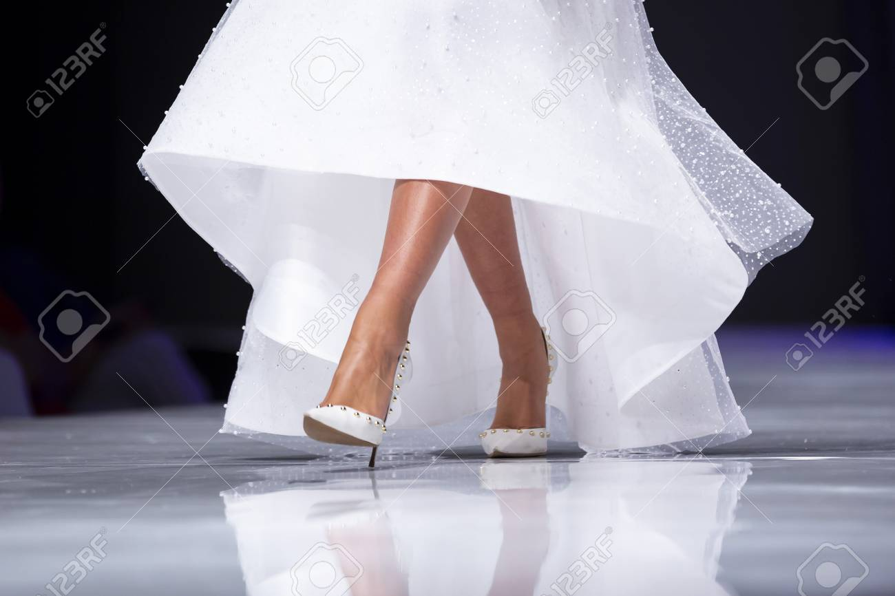 Female model walks the runway in white dress during a Fashion..