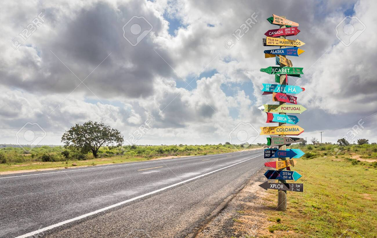 Funny different world directions signpost with distance to many different countries - 123700975