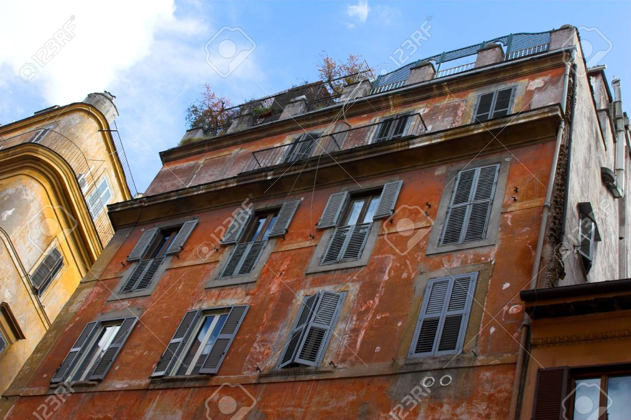 dilapidated front of red building with bars at the windows in Rome Stock Photo - 1808199