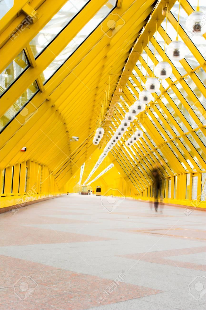 Yellow glass corridor in bridge and people walking Stock Photo - 2032513