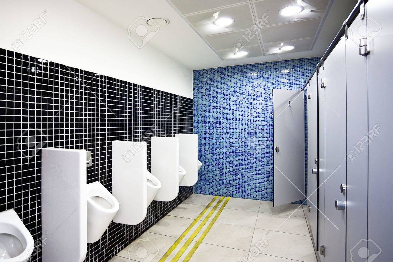 View To Public Toilet With Grey Cubicles And White Urinals Stock Photo
