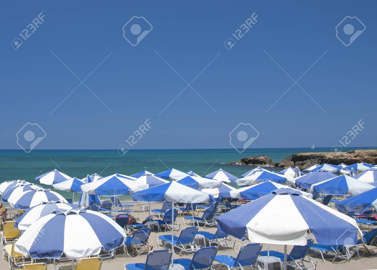 Blue and White Beach Umbrellas on a Beach in Greece under a blue summer sky Stock Photo - 9762104
