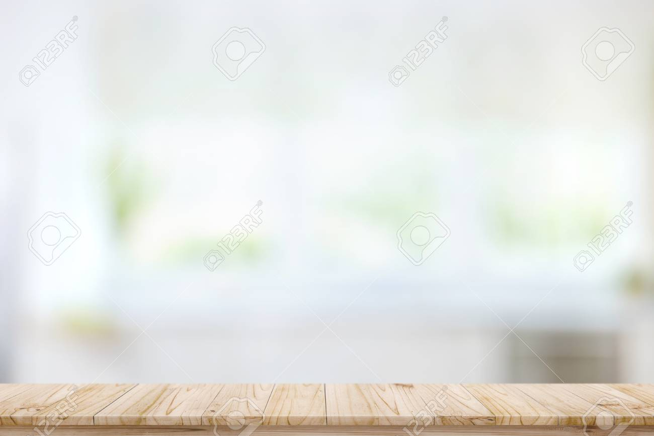 Empty wood table top on blur kitchen window background. For product..