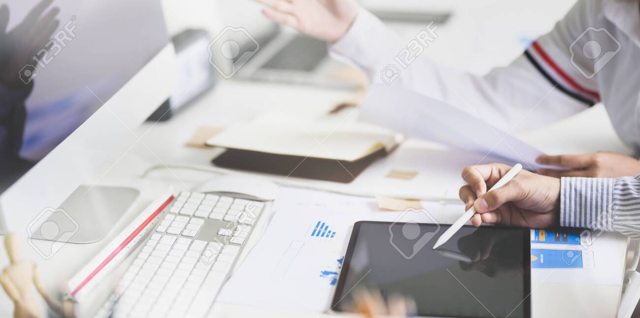 Young development team consulting their project while using tablet in modern office - 128373672