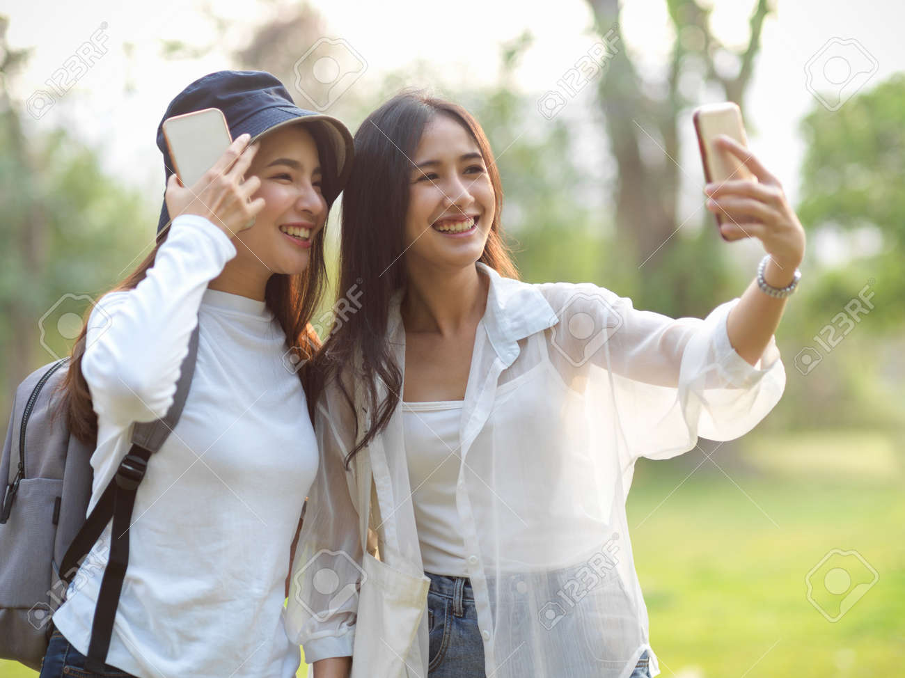 Portraits of two young female travellers taking photo with smartphone while walking around in the park - 167079531