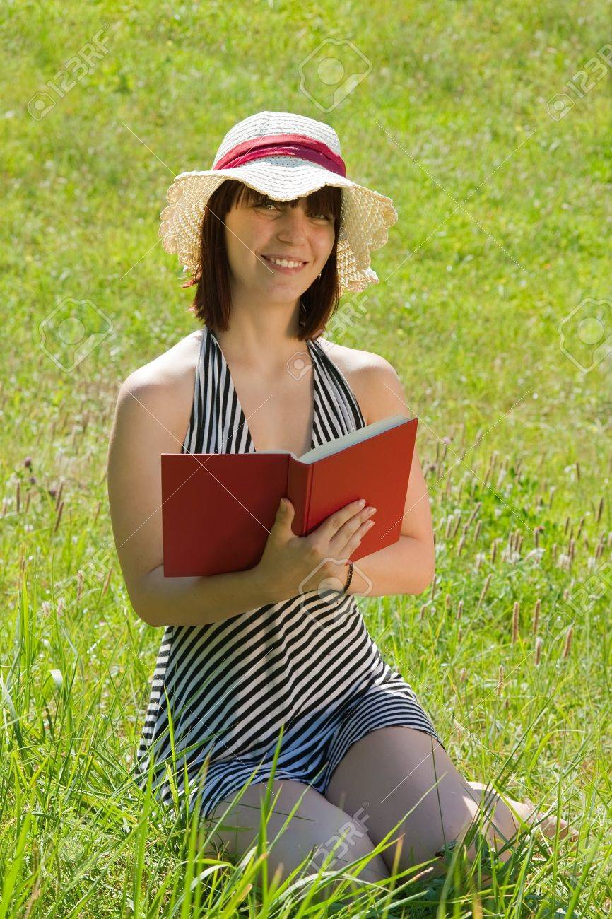 short-haired teen girl reading in meadow grass Stock Photo - 7410195