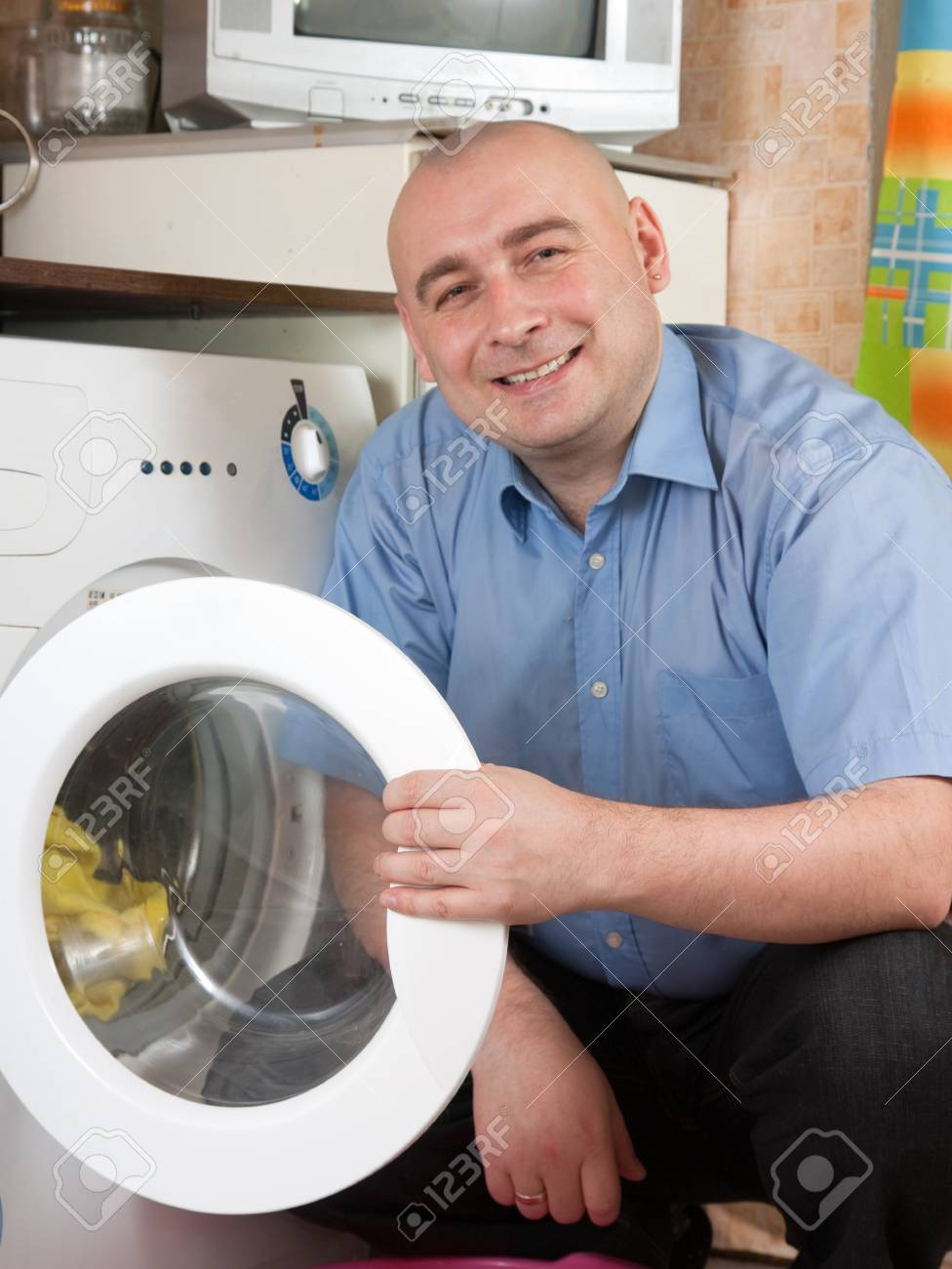 Smiling men loading the washing machine. Cleaning and Laundry Stock Photo - 9734758