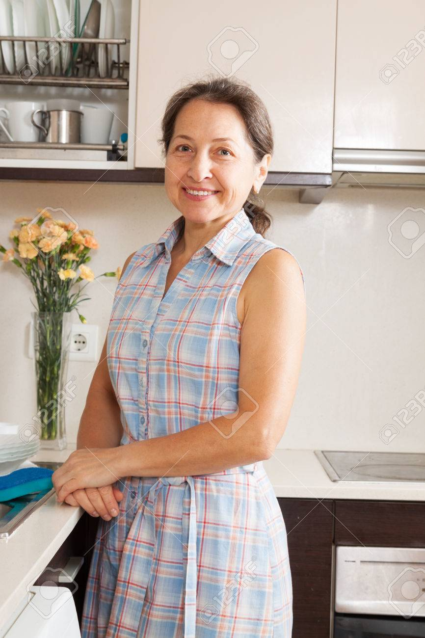 mature woman smiling at her big kitchen stock photo, picture and