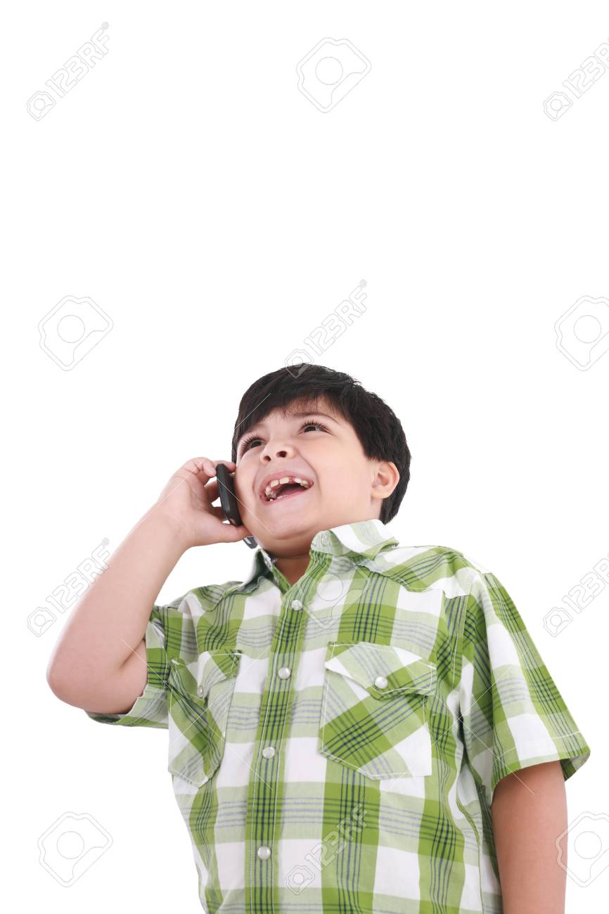 Beautiful little boy  laughs and talks by mobile phone. Stock Photo - 10908493