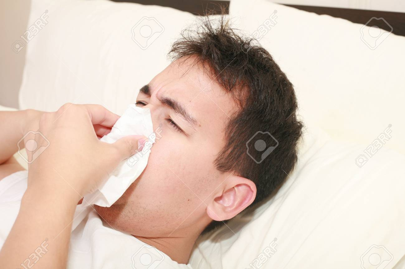 Sick man blowing his nose lying on his bed at morning Stock Photo - 12222318