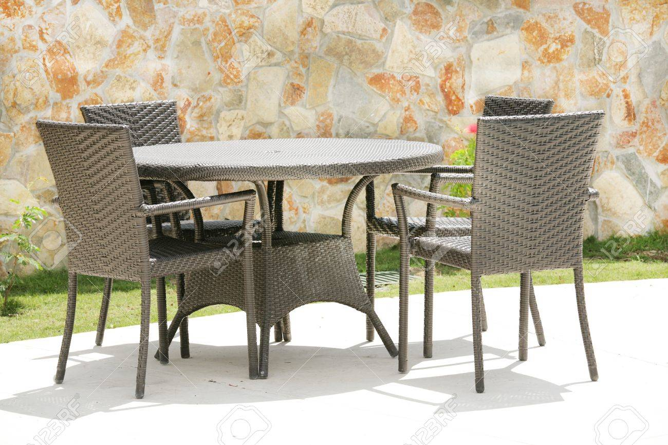 Table and chairs in a tropical garden with a stone wall texture Stock Photo - 12838253