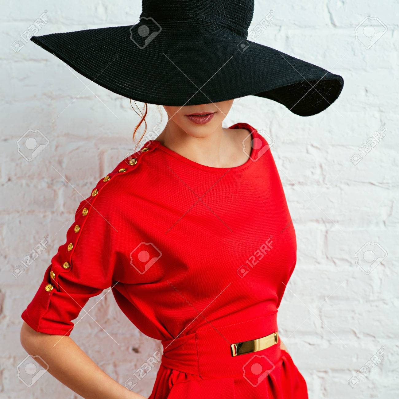 Beautiful young fashionable woman posing in red dress and black hat. Vogue  style Stock Photo 7fb1ca56eb1