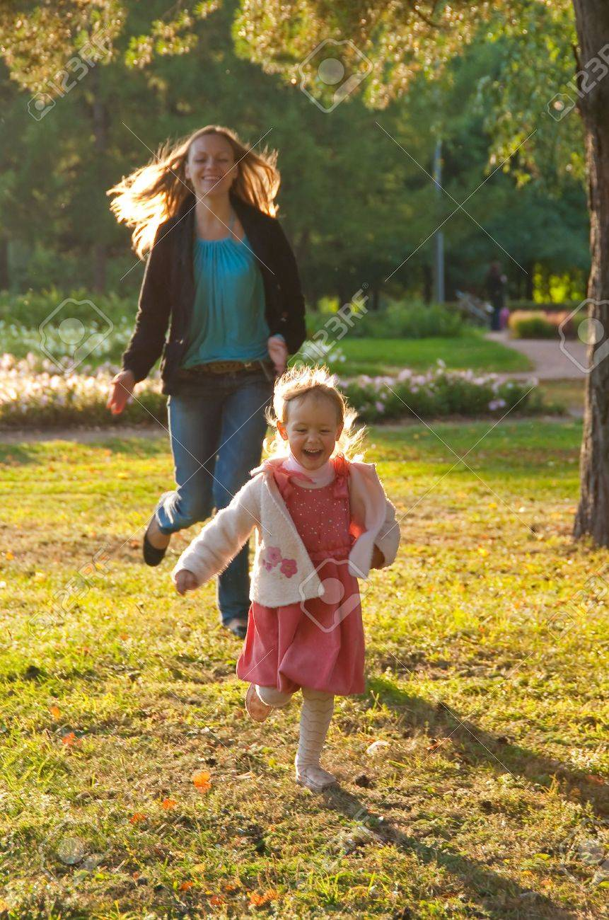 Young mother and daughter playing in the summer park Stock Photo - 6539917