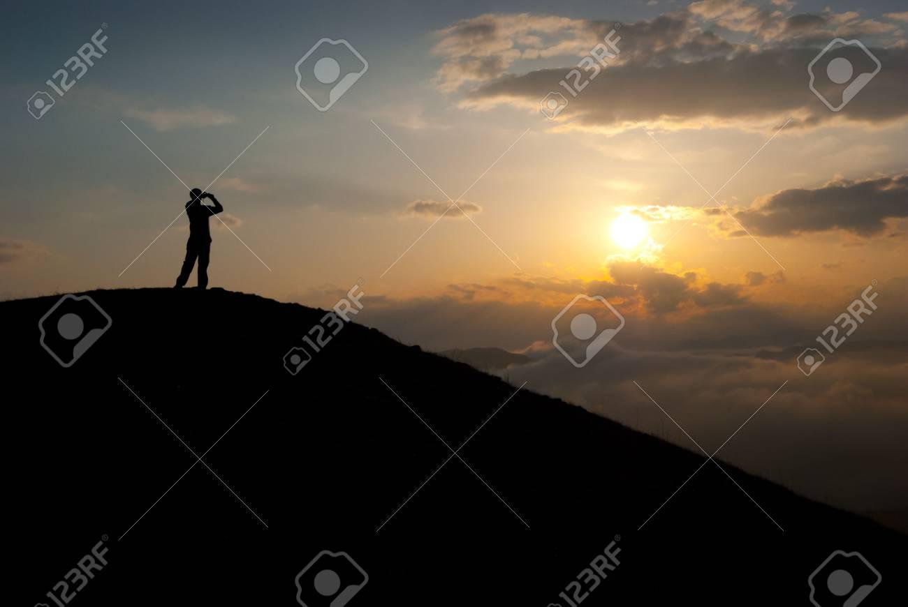 Man at the peak watching the sun Stock Photo - 6789453
