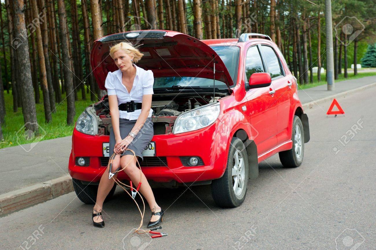 Ragazza bionda impotente seduto sul cofano in attesa di servizio di auto Archivio Fotografico - 9954950