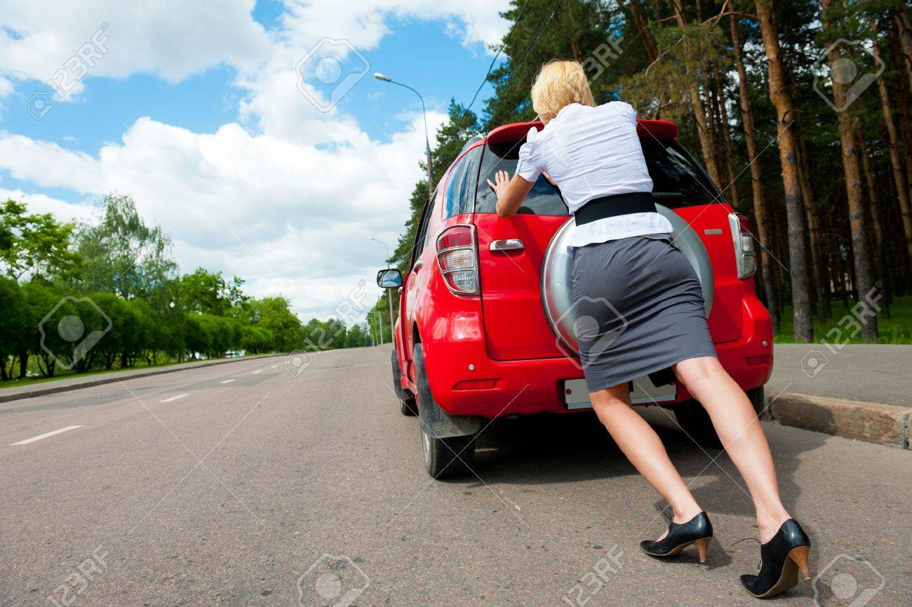 Blonde girl pushes her broken car to the car service - 9954953