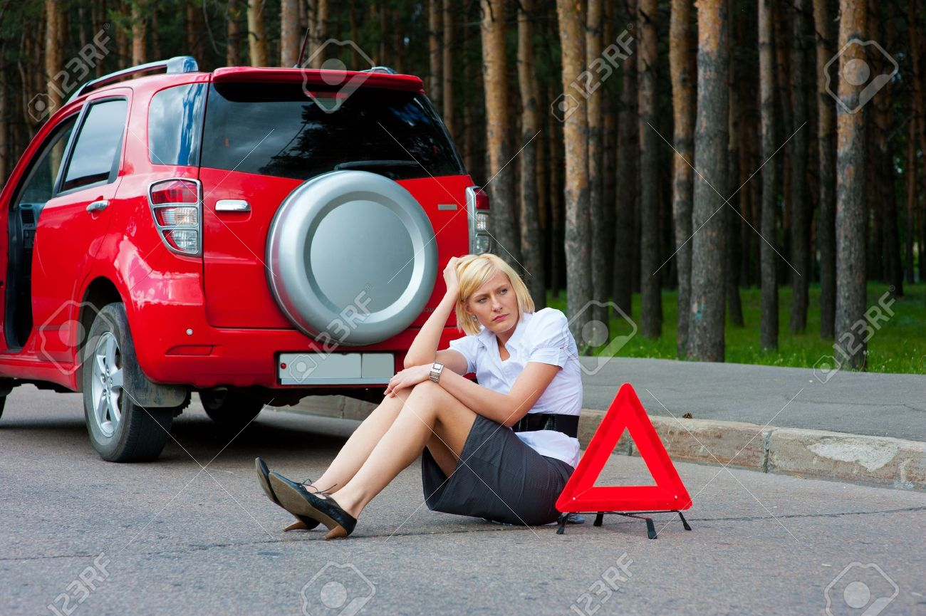 Blonde girl helplessly sitting on the road waiting for car service - 9954956