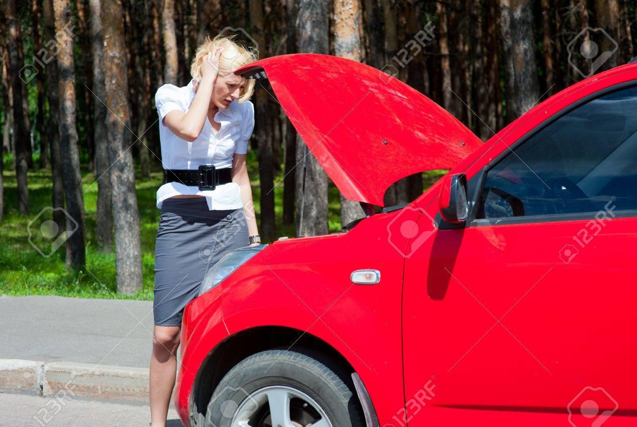 Blonde girl looks under the hood of a broken car Stock Photo - 9955118