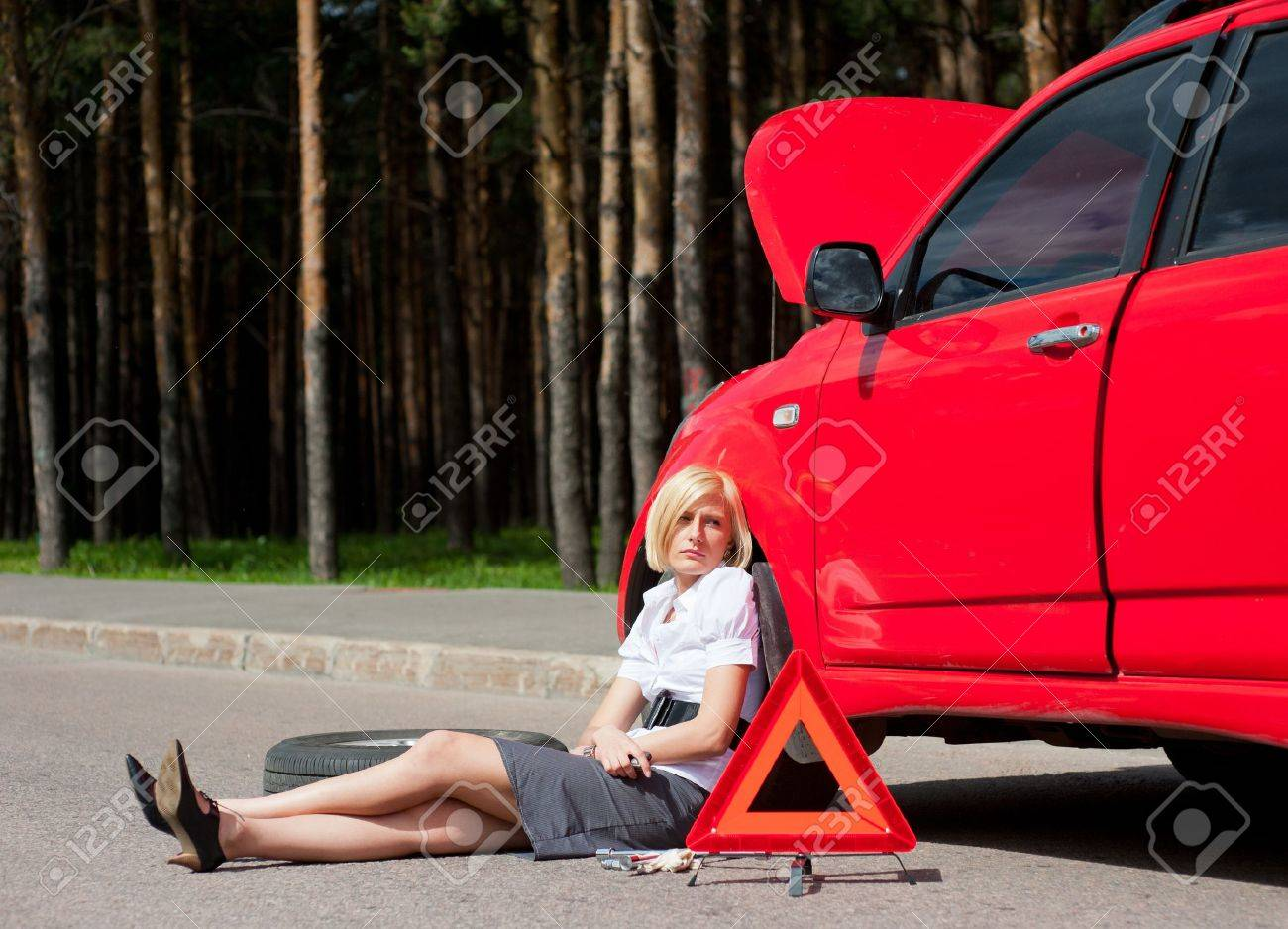 Blonde girl sitting near broken car and waiting for help Stock Photo - 10065378