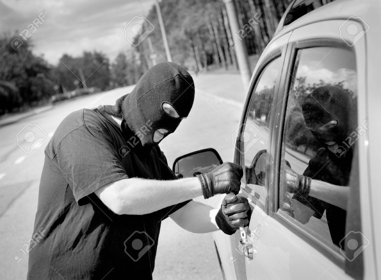 Thief breaks into a car door on the street - 10065367
