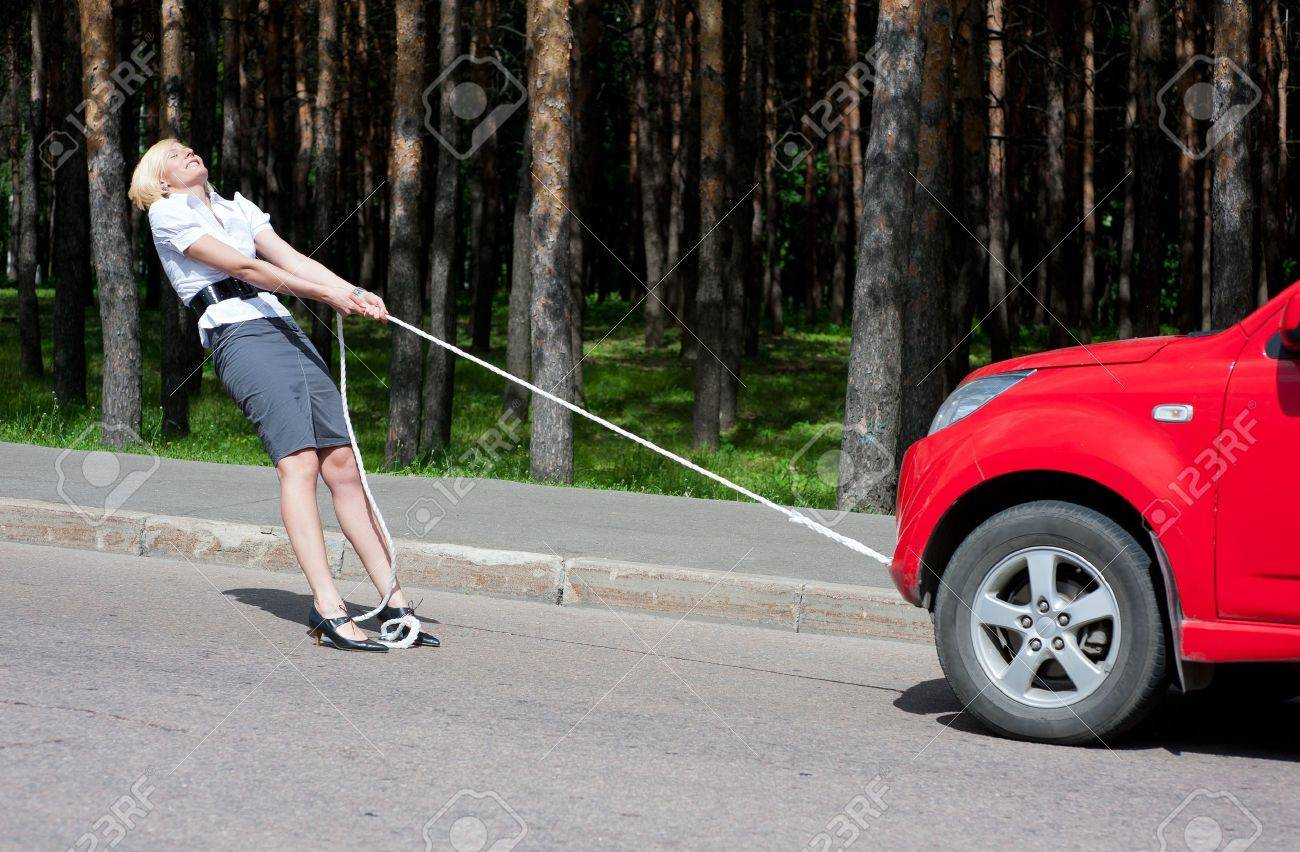 Blonde girl pulls a broken car with a rope - 10065429