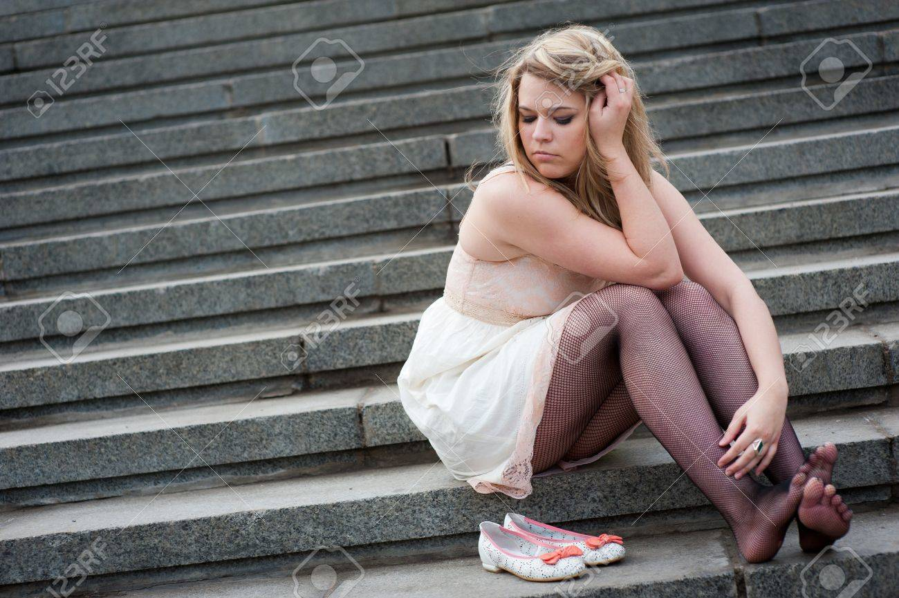 Sad lonely girl sitting on the steps Stock Photo - 10065416