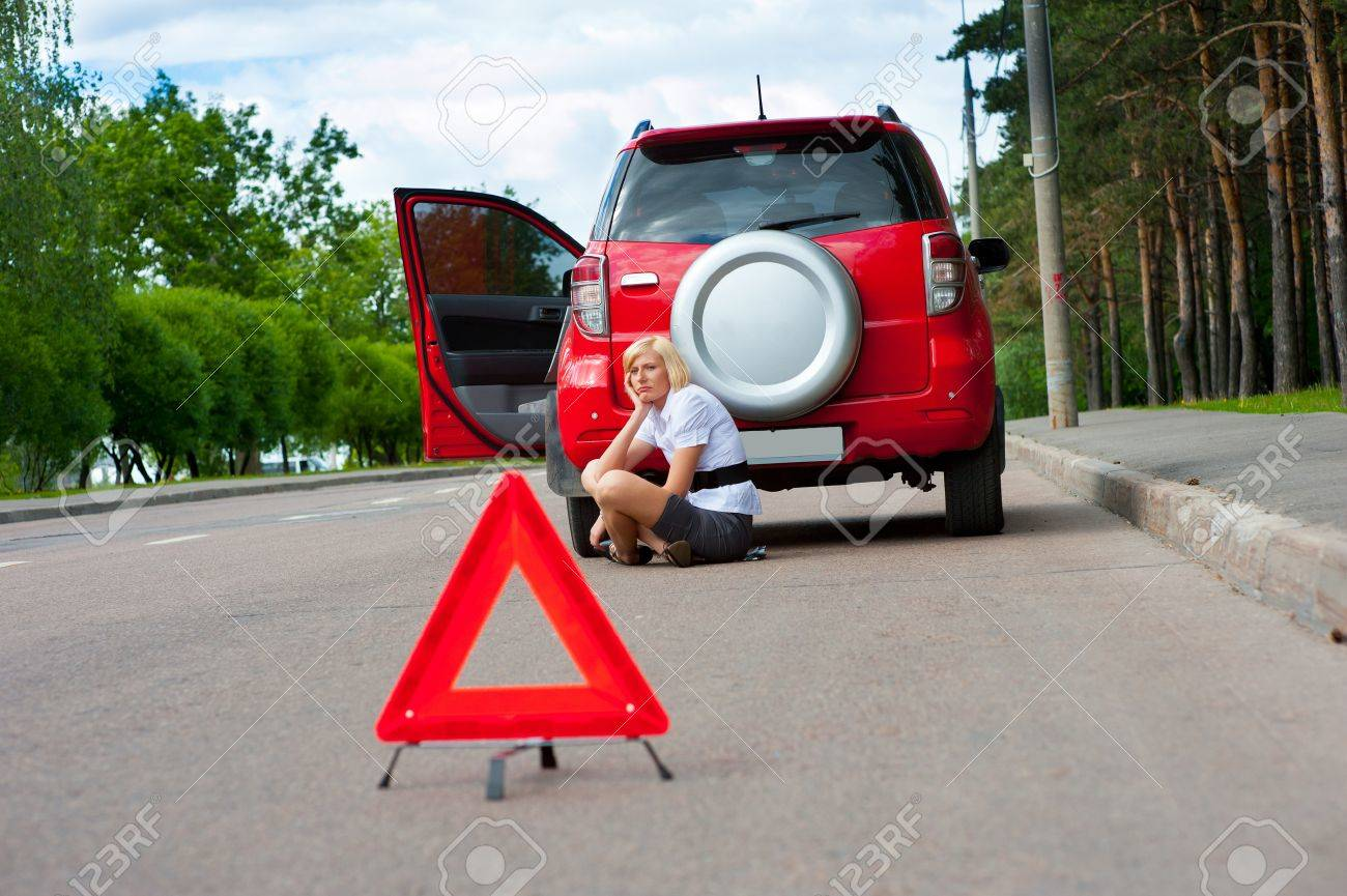 Blonde girl helplessly sitting on the road waiting for car service Stock Photo - 10472129