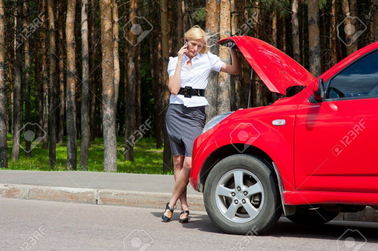 Blonde woman calls to car service on a road - 10504114