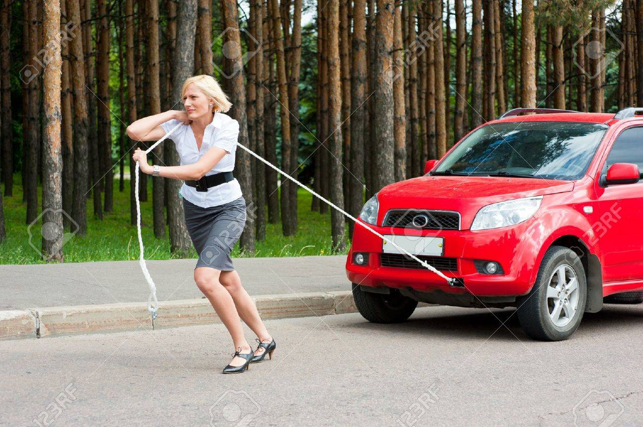 Blonde girl pulls a broken car with a rope Stock Photo - 10504120