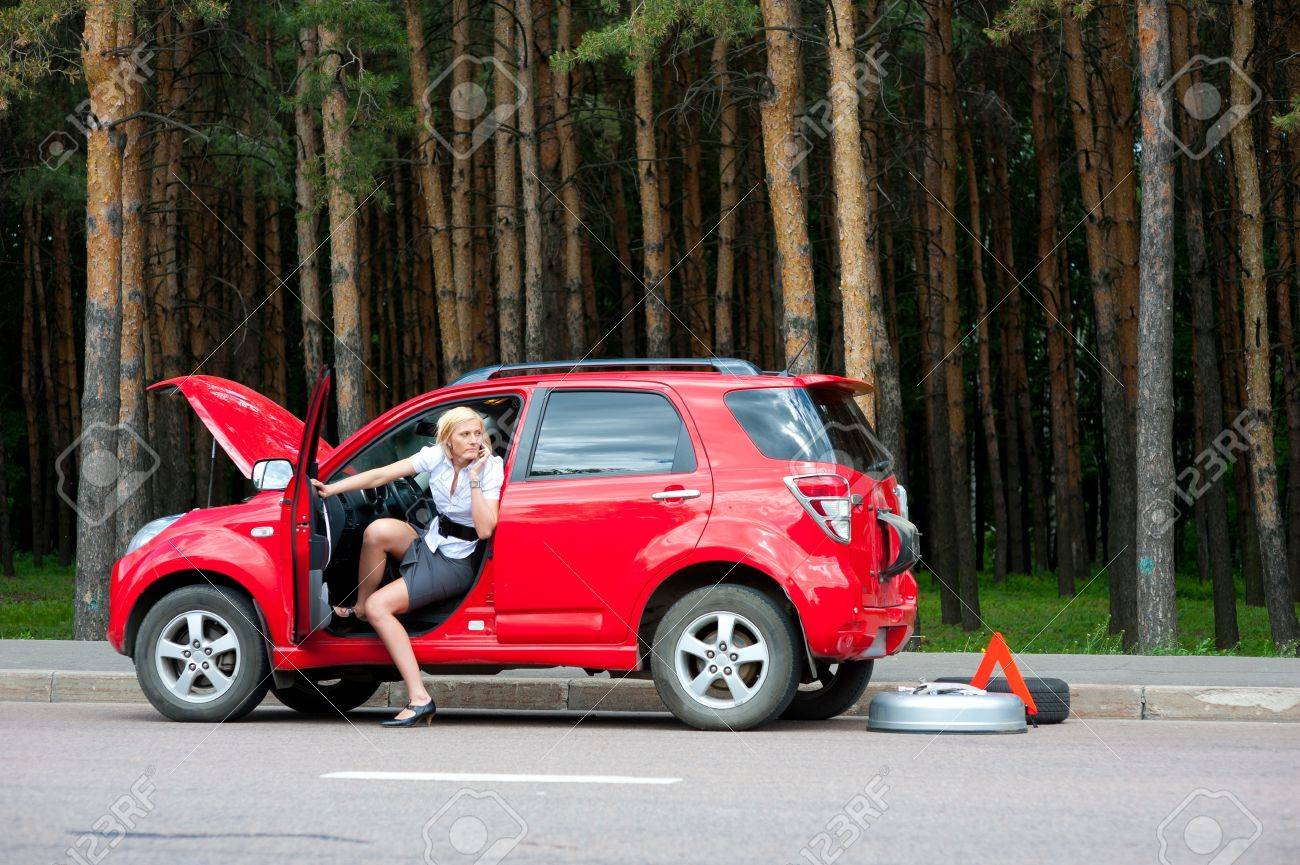 Blonde woman calls to car service on a road Stock Photo - 10504122