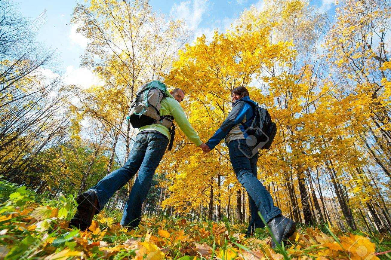Happy young couple with backpacks in the park. Fall. - 10992153