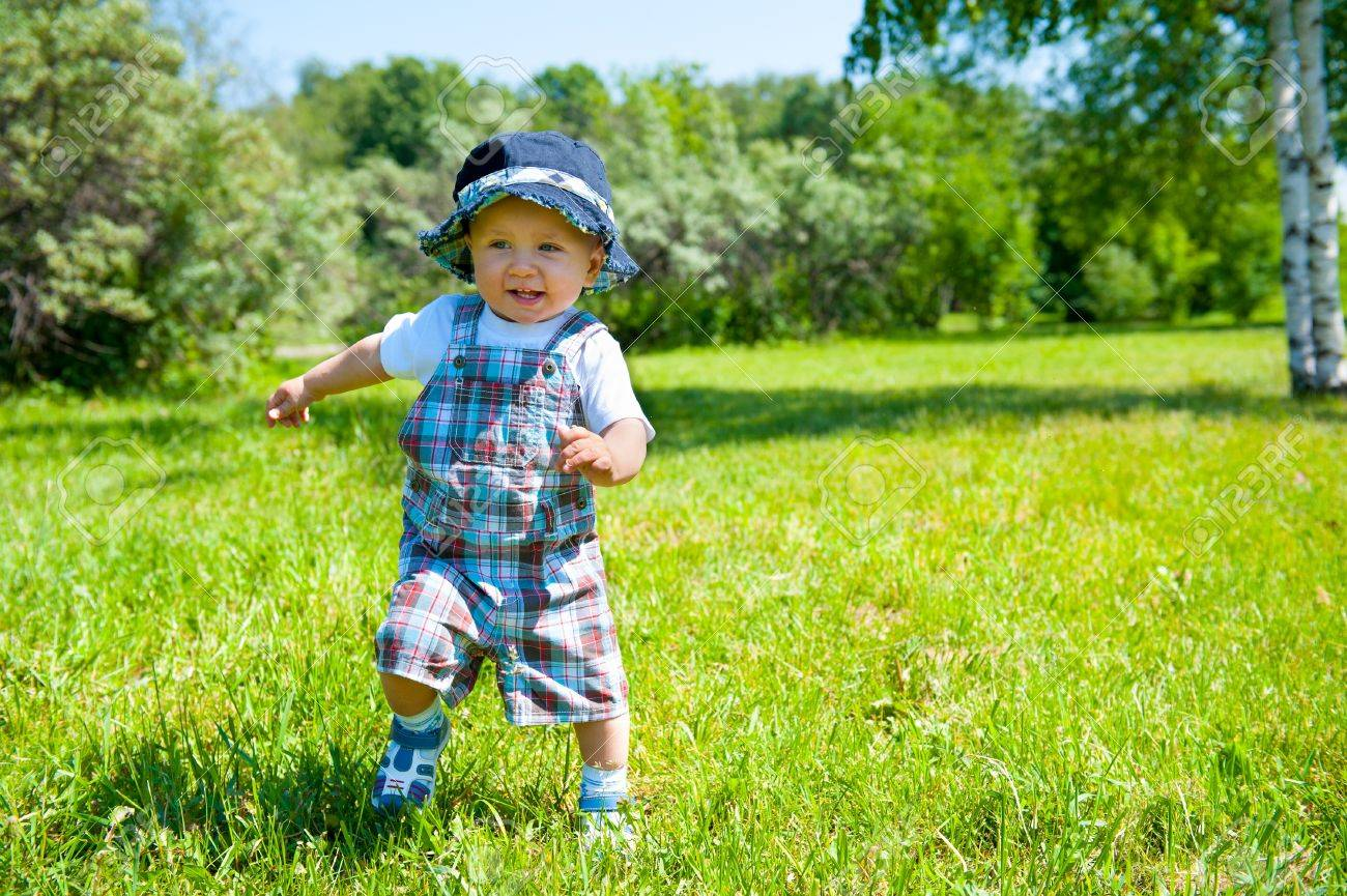 Toddler taking first steps in a park - 14155660